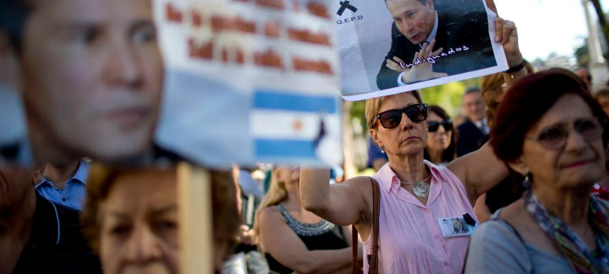 demonstrators hold images of the late prosecutor Alberto Nisman