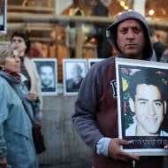 Israeli protesters display photos of victims of Palestinian terror.