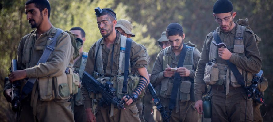 Religious IDF soldiers pray during training.