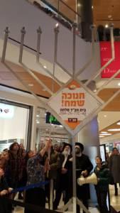 Ginny Nissenbaum lights the Chabad menorah at Malcha Mall (Tsivya Fox-Dobuler)