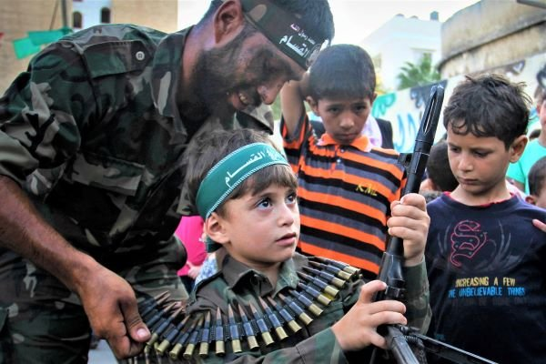 Palestinian boy holds a weapon